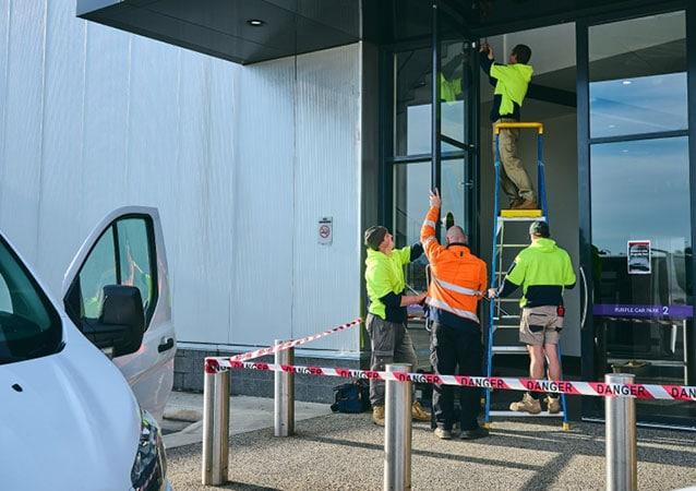 technicians repairing a store front door